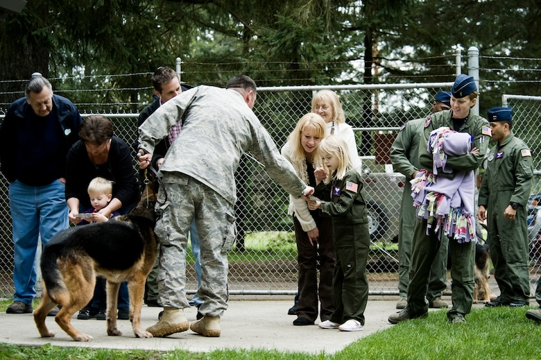 Kaylie Bergen, age 6, and her brother Dylan, 3, are handed military working dog trading cards while visiting the 62nd Security Forces MWD kennels May 11 as part of McChord Field's Pilot for Day program. (U.S. Air Force Photo/ Abner Guzman)