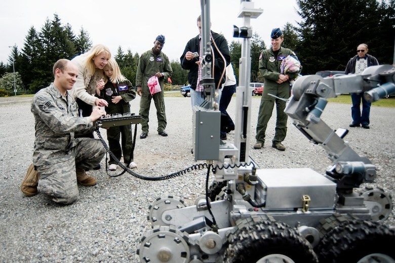 Pilot for a Day candidate Kaylie Bergen, age 6, and her family look on as Senior Airman Nathan Howard, 62nd Civil Engineer Squadron, demonstrates the capabilities of an EOD robot May 11. (U.S. Air Force Photo by Abner Guzman)