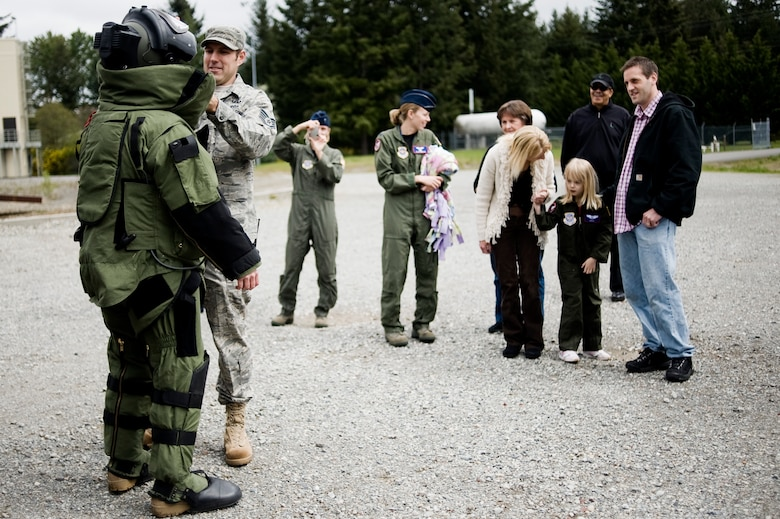 Pilot for a Day candidate Kaylie Bergen, age 6, and her family look on as Staff Sgt. Mark Walker and Airman 1st Class Mark Stafford, 62nd Civil Engineer Squadron, demonstrate the capabilities of an EOD protective bomb suit May 11. (U.S. Air Force Photo by Abner Guzman)