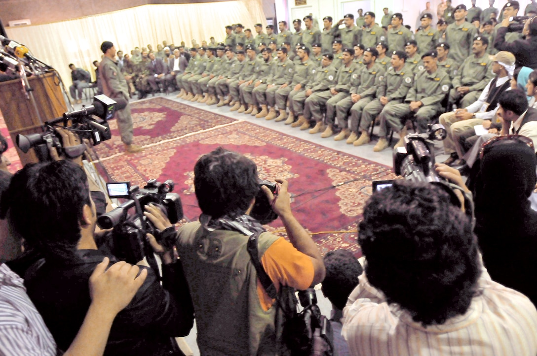 Afghan soldiers listen to speeches and are photographed by local and international press during a transition ceremony May 5, 2010, at a conference center on the Afghan National Army Air Corps base in Kabul, Afghanistan. The soldiers are from the Ministry of Interiors Air Interdiction Unit. (U.S. Navy photo/Petty Officer 2nd Class David Quillen)