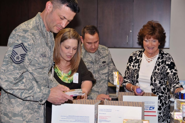 (Left to right) Senior Master Sgt. Peter Padilla, Air Force Operational Test and Evaluation Center First Sergeant, helps put together care packages for AFOTEC's deployed members with Mrs. Brandi Miller, MSgt. Scott Miller, AFOTEC Superintendent of Executive Support, and AFOTEC Key Spouse Program leader Mrs. Vivie Sargeant. (Photo by George Diamond).