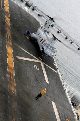 A CH-46E Sea Knight from Marine Medium Helicopter Squadron 165 (Reinforced), 15th Marine Expeditionary Unit, lands on the flight deck of USS Peleliu for embarkation before deploying with the 15th MEU for the last time. The MV-22 Osprey will replace the CH-46E on future deployments.