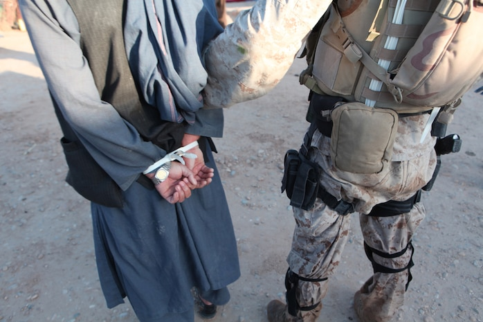 An Afghan Counter Narcotic National policeman holds the Afghan government's primary drug kingpin in Marjah, Afghanistan May 18. The mission, a team effort between the Marines, Drug Enforcement Administration and Counter Narcotic Police of Afghanistan, nabbed high-level drug traffickers.::r::::n::