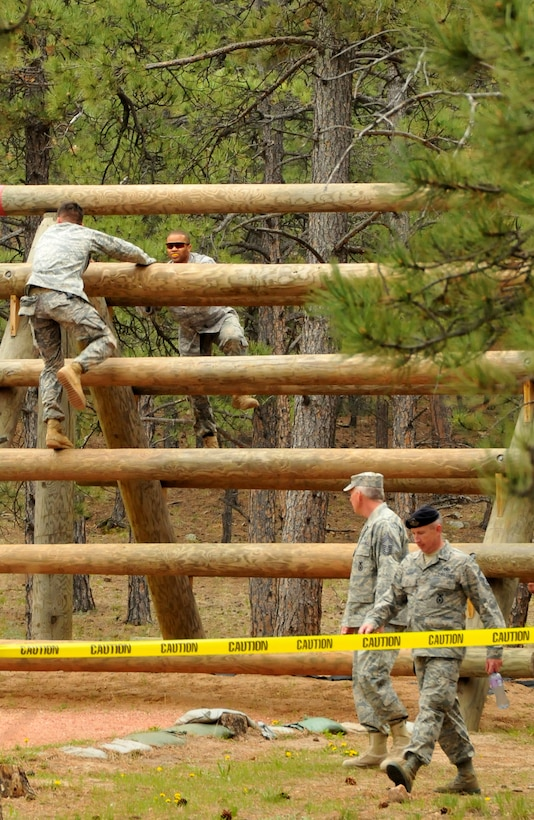 Tech. Sgt. Leslee Williams (right) climbs up one of the Assault Course obstacles as Staff Sgt. Alexr Andriyanov (left) descends on the other side during a practice run on the Assault Course at the U.S. Air Force Academy, Colo., May 18, 2010. Both are Guardian Challenge 2010 competitors from the Space and Missile Systems Center's 61st Security Forces Squadron at Los Angeles Air Force Base. (Photo by Lou Hernandez)