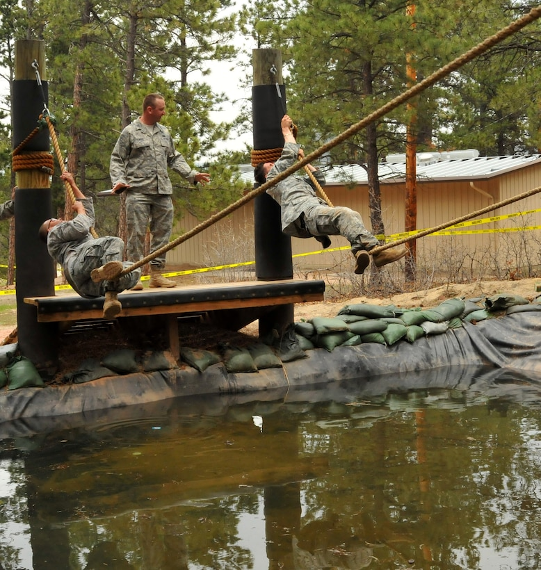 Tech. Sgt. Leslee Williams (left) goes hand over hand on the rope while hanging over water at the Assault Course as Staff Sgt. Alex Andriyanov (right) reaches the end of his rope during a practice run on the Assault Course at the U.S. Air Force Academy, Colo., May 18, 2010. Both are Guardian Challenge 2010 competitors from the Space and Missile Systems Center's 61st Security Forces Squadron at Los Angeles Air Force Base. (Photo by Lou Hernandez)