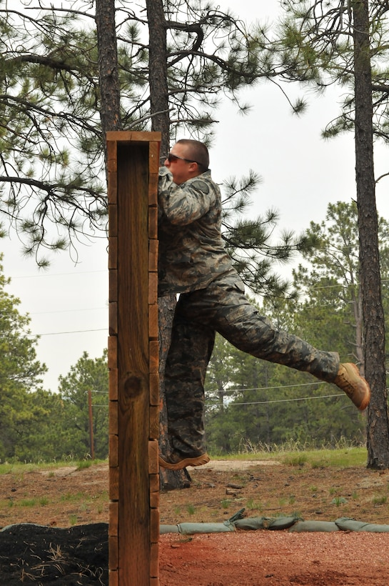 Department of Defense Officer Steven Haymes jumps up a wall during a practice run on the Assault Course at the U.S. Air Force Academy, Colo., May 18, 2010. Officer Haymes is a Guardian Challenge 2010 competitor from the Space and Missile Systems Center's 61st Security Forces Squadron at Los Angeles Air Force Base. (Photo by Lou Hernandez)