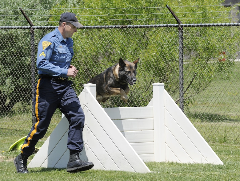 Sean Dawson, K-9 Unit South Region assistant squad leader, leads his dog Rip through a obstacle course during the obedience portion of the K-9 competition at Joint Base McGuire-Dix-Lakehurst May 13. Various activities were held throughout JB MDL as part of National Police Week, which is held annually across the nation. (U.S. Air Force photo/Carlos Cintron)