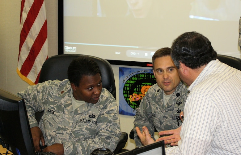 Maj. Janis Mack and Lt. Col. Ken Roller, 90th Information Operations Squadron, get a tutorial on the Guardian Challenge network from the creators, Jim Collins and Master Sgt. James Boyd (not pictured).