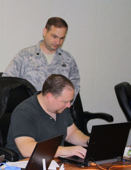 Dallas Davies, 346th Test Squadron works on a Guardian Challenge scenario, while the commander, Lt. Col. Fred Baier, watches. (US Air Force photo)