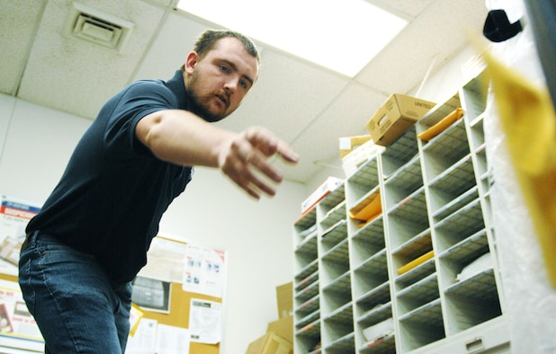 Donald Morris Jr., an employee at the Official Mail Center, sorts letters and packages that arrived earlier that morning.  After sorting, the mail is distributed around the base.