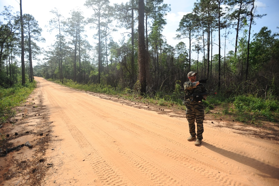 Mathew Comeau, 1st Special Operations Support Squadron Range Support flight opposition forces member, scans the road for footprints during combat survival training at an undisclosed location in the Eglin Range, Fla., May 13, 2010. OPFOR provides support capabilities to 1st Special Operations Wing aircraft and ground assets, and, when available, other Air Force Special Operations Command, Air Force and joint partners who request them.  (DoD photo by U.S. Air Force Senior Airman Matthew Loken)