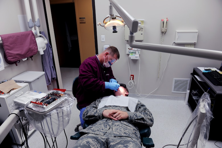 MOODY AIR FORCE BASE, Ga. -- Staff Sgt. Steven Smith, 23rd Aeromedical Dental Squadron dental technician, cleans the teeth of Airman 1st Class Edward Huffman, 822nd Security Forces Squadron member, during a routine dental cleaning here May 12. Airmen are required to have a routine dental cleaning and check-up annually. (U.S. Air Force photo by Airman 1st Class Joshua Green/RELEASED)