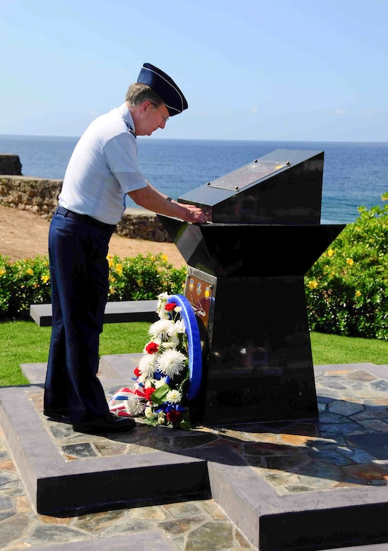 """Lt. Gen. Frank G. Klotz places his """"commander's coin"""" on the memorial to RAIDR 21 May 14, 2010, in Agana, Guam, after laying a wreath at the site commemorating the B-52 crew that was lost when their B-52 went down in the Pacific on Guam's Liberation Day on July 21, 2008. General Klotz is the commander of Air Force Global Strike Command. (U.S. Air Force photo/Airman 1st Class Jeffrey Schultze)"""