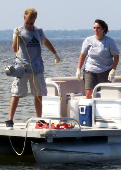 Melissa Hoover and Jordan Gibson of Brown, Burdine and Associates collect sediment samples, from Choctawhatchee Bay, using a stainless steel Ponar sampling device. The base is collecting samples and documentation to establish a baseline condition of the 18 miles of Santa Rosa Island that Eglin controls along with the miles of shoreline along Choctawhatchee Bay to ensure the base has a strong understanding of its coastal natural resources.  (Photo by Jonathan Kramer.)
