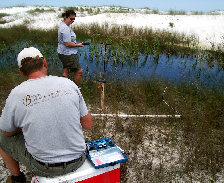 Melissa Hoover and Tony Schmucker of Brown, Burdine and Associates collect field samples from wetlands near the Eglin Beach Club on Santa Rosa Island.  Surface water and sediment samples were collected from four separate wetlands on the island. The base is collecting samples and documentation to establish a baseline condition of the 18 miles of Santa Rosa Island that Eglin controls along with the miles of shoreline along Choctawhatchee Bay to ensure the base has a strong understanding of its coastal natural resources.  (Photo by Jordan Gibson.)