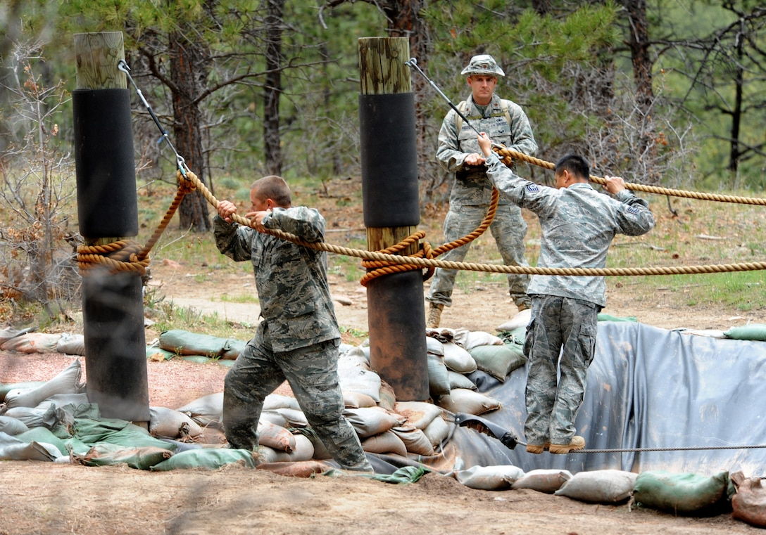 Department of Defense Officer Steven Haymes  (left) and Tech. Sgt. Rochanapan Silpe (right) hold onto the ropes while passing a water pond as an official looks on at the Guardian Challenge 2010's obstacle course May 19 during the final portion of the security forces competition. Both are members from the Space and Missile Systems Center's 61st Security Forces Squadron. (Photo by Lou Hernandez)