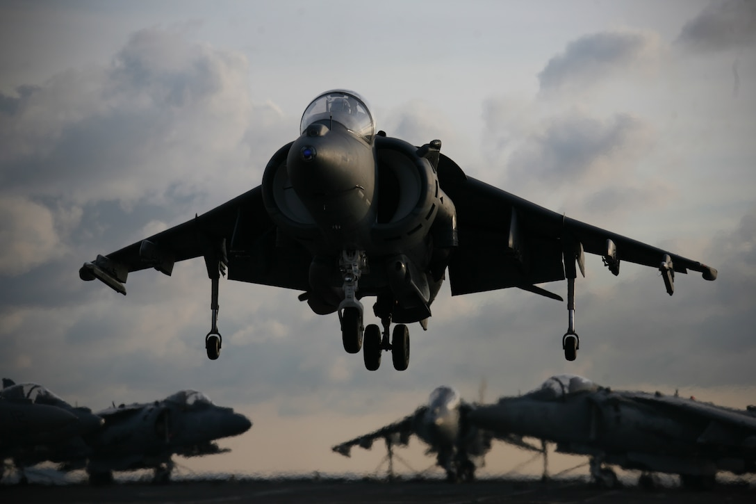 """Lt. Col. Terence J. Dunne, a pilot and readiness officer with Marine Aircraft Group 14, lands an AV-8B Harrier onto the HMS Ark Royal, the British Royal Navy's flagship aircraft carrier, May 21.  ::r::::n::""""The ship presented pilots a rare challenge of taking off from the its 12-degree ramped deck,"""" said Dunne."""