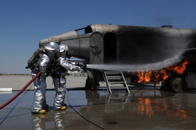 """Cpl. Jordan Rowley, left, Marine Wing Support Squadron 371 firefighter, helps Laura Temple, Marine Attack Squadron 211 spouse, put out a controlled fire on a mock aircraft at the Marine Corps Air Station in Yuma, Ariz., here during VMA-211's Jane Wayne Day May 21, 2010. More than 20 spouses spent the day touring the station and experiencing some of what Marines go through. """"I've reached a whole new level of respect for my husband and every other Marine,"""" said Christina Belanger, squadron spouse."""