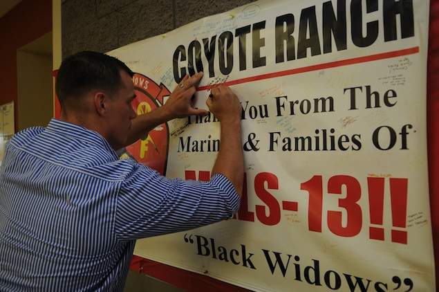 Cpl. Dylan Cox, Marine Aviation Logistics Squadron 13 aircraft maintenance support technician, signs a poster May 22, 2010, thanking the residents of Coyote Ranch in Yuma, Ariz., for supporting MALS-13. For the past four years, the residents of Coyote Ranch, a retirement community, have supported MALS-13 with care packages and social events. The local retirees cooked the Marines a celebratory dinner, an event which for some Marines was the first time they met the people behind packages.
