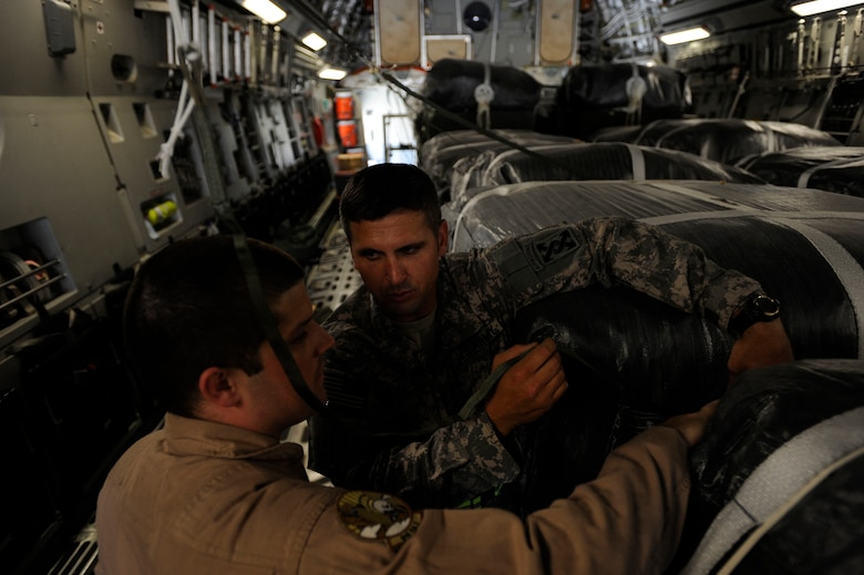 Army Sergeant 1st Class Jonathan Hall, right, an airdrop inspector assigned to the 824th Quartermaster Company, Det. 8, speaks with Staff Sgt. Bryan Carey, a C-17 Globemaster III loadmaster assigned to the 816th Expeditionary Airlift Squadron, regarding his findings during a joint inspection of container-delivery-system bundles May 9, 2010, at a base in Southwest Asia. (U.S. Air Force photo/Staff Sgt. Manuel J. Martinez/released)