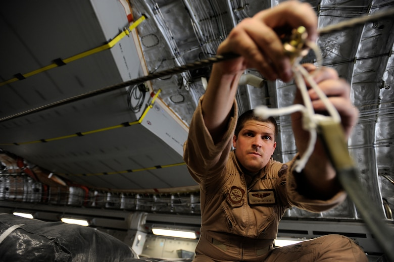Staff Sgt. Bryan Carey, a C-17 Globemaster III loadmaster assigned to the 816th Expeditionary Airlift Squadron, hooks parachute draw cords to container-delivery-system bundles prior to take off for an airdrop mission May 9, 2010, at a base in Southwest Asia. (U.S. Air Force photo/Staff Sgt. Manuel J. Martinez/released)
