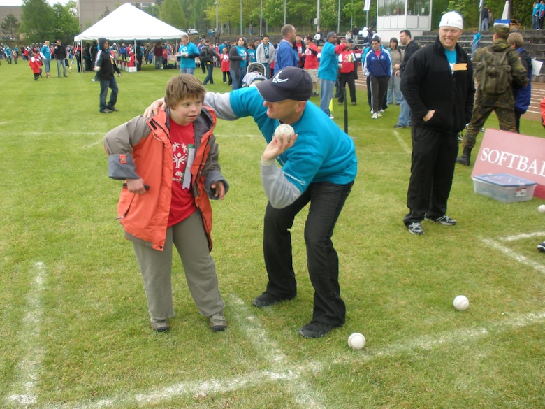 KAISERSLAUTERN, Germany – Master Sgt. Brian Rogers, 726th Air Mobility Squadron, demonstrates the proper technique in throwing a softball to a participant in the Special Olympics Day May 12 in Kaiserslautern, Germany. Sergeant Rogers volunteered along with other member of Spangdahlem's local Airlift Tanker Association chapter, the Halvorson Chapter. (U.S. Air Force photo/Shari Sims)