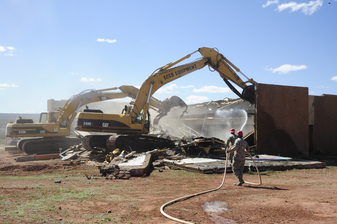 Members of the 203rd Red Horse Squadron, Virginia Beach Va., demolish the condemned dining hall at St. Michael's Association for Special Education school in Window Rock, Ariz., on May 19, 2010. The Red Horse team, along with the 240th Civil Engineering Flight, 140th Wing, Colorado Air National Guard, are at St. Michael's breaking ground on new facilities across campus. The effort to upgrade the complex for physically and mentally handicapped children and adults is part of the National Guard's Innovative Readiness Training program, a civil-military affairs program that links military units with civilian communities for humanitarian projects. Throughout the next five years several Civil Engineering teams across the Air National Guard will rotate every two weeks to help this under privileged school.   (U.S. Air Force photo by Staff Sgt. Nicole Manzanares /RELEASED)