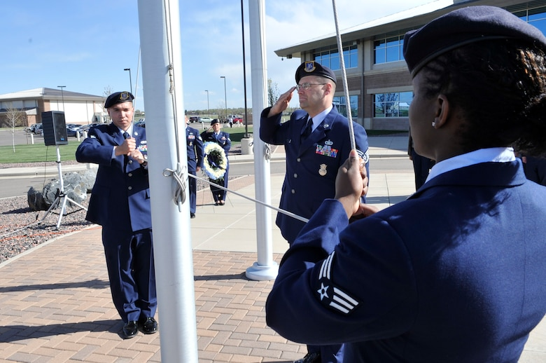 BUCKLEY AIR FORCE BASE, Colo. -- Senior Airman Steven Pillman, Staff Sgt. Thomas Gehres and Senior Airman Lauren Myrick, all 460th Security Forces Squadron, lower the American flag during a National Police Week retreat ceremony May 10. (U.S. Air Force photo by Airman 1st Class Paul Labbe)