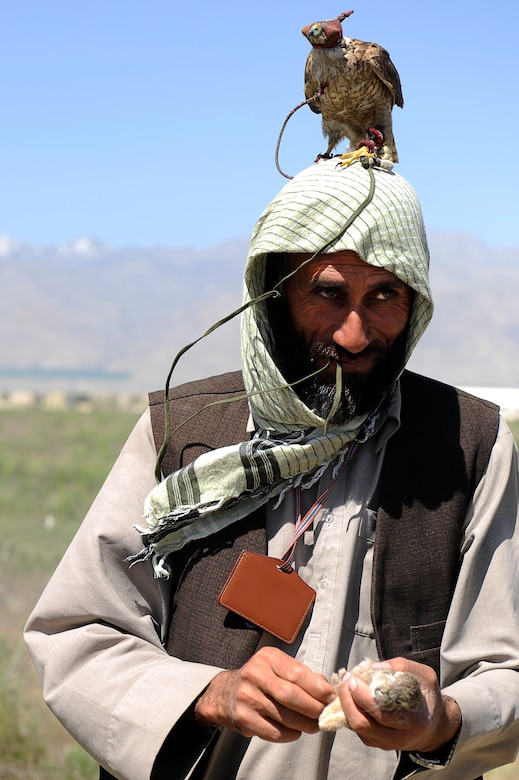 Mohammed a local contractor and his falcon Basha hold a rabbit they capture near the flight