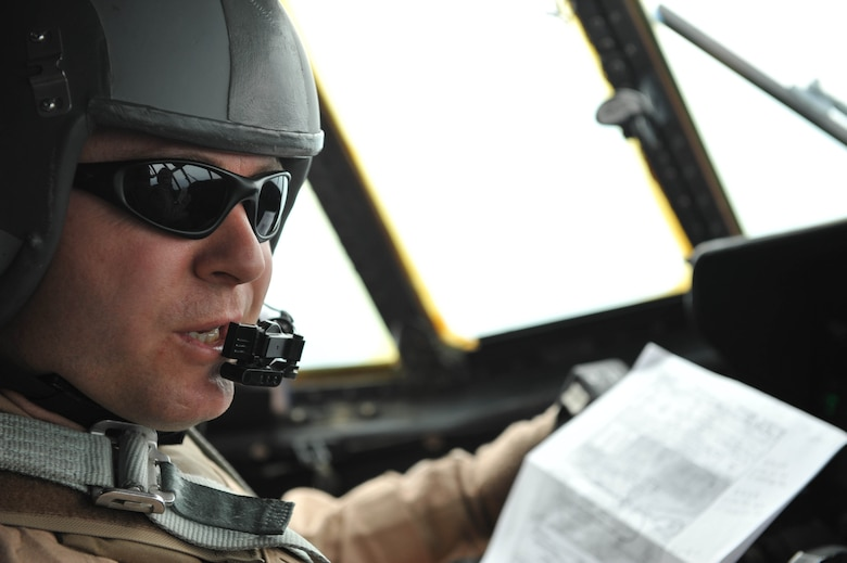 U.S. Air Force C-130 Hercules pilot, Maj. Kurt Amundson, talks with his co-pilot before landing at Dushanbe International Airport Tajikistan, May 21, 2010.  Major Amundson is deployed to the 774th Expeditionary Airlift Squadron, Bagram Airfield, Afghanistan.  (U.S. Air Force photo/Staff Sgt. Quinton Russ/released)
