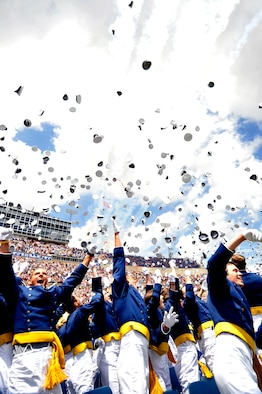 Newly commissioned second lieutenants throw their hats into the air to celebrate graduation in Falcon Stadium at the Air Force Academy May 26, 2010. The Thunderbirds U.S. Air Force Air Demonstration Team performed at the conclusion of the ceremony. (U.S. Air Force photo/Bill Evans)