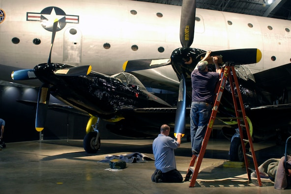 DAYTON, Ohio (05/2010) -- In preparation for the 60th anniversary of the Korean War, the National Museum of the U.S. Air Force is renovating its Korean War exhibit. Here, restoration specialists paint stenciling on the F-82. (U.S. Air Force photo)