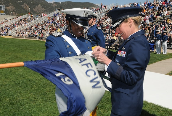 Cadet 1st Class Nathan Dial and Brig. Gen. Dana Born affix a 2010 Outstanding Squadron banner to Cadet Squadron 19's guidon during the Individual Awards Parade at the U.S. Air Force Academy's Stillman Parade Field May 24, 2010. Cadet Dial was the Fall 2009 Cadet Wing commander. General Born is the dean of the faculty. (U.S. Air Force photo/Rachel Boettcher)