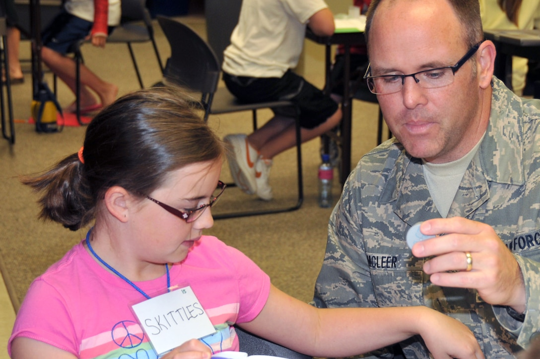 Senior Master Sgt. Donald J. McLeer and his daughter, Madison, call sign Skittles, measure a solution to be used to make slime during STARBASE summer session at Joe Foss Field, SD May 26. (Air Force photo by Master Sgt. Nancy J. Ausland - released)