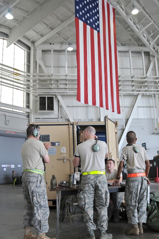 Air cargo specialists from the notional 104th Air Expeditionary Wing discuss their upcoming duties May 19, 2010 while standing in front of a large American Flag inside the Main Hanger at the Gulfport Combat Readiness Training Center in Gulfport, Miss. Airmen from the Kentucky Air National Guard's 123rd Airlift Wing, the active-duty Air Force's 317th Airlift Group at Dyess Air Force Base, Texas, and the Air Force Reserve's 70th Aerial Port Squadron from Homestead Air Reserve Base, Fla., all combined to form the 104th during an Air Mobility Command Operational Readiness Inspection here. (U.S. Air Force photo/Tech. Sgt. Dennis Flora) (Released)