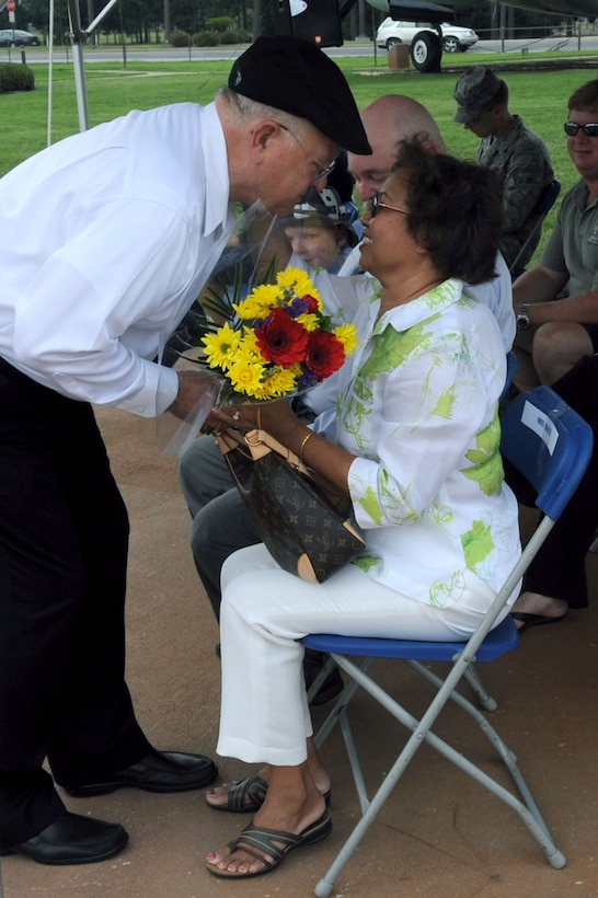 Bob Baker, 1st Special Operations Support Squadron's airfield manager, hands his wife, Im, a bouquet of flowers during his retirement ceremony at the Airpark at Hurlburt Field, Fla., May 27, 2010. Mr. Baker completed his civil service career on the 55th anniversary of the day he enlisted in the Air Force. (DoD photo by U.S. Air Force Airman Caitlin O'Neil-McKeown)