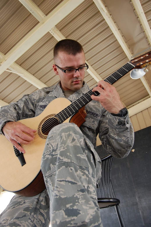 U.S. Air Force Staff Sgt. Israel Poire, 386th Expeditionary Civil Engineer Squadron structural journeyman, practices his guitar May 28, 2010 at an air base in Southwest Asia. The fingerstyle guitarist is a Mustang, Okla. native deployed from the 137th Civil Engineer Squadron at Will Rogers Air National Guard Base, Okla. (U.S. Air Force photo by Staff Sgt. Lakisha Croley/Released)
