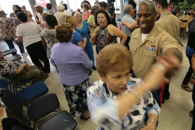 NEW YORK -- Capt. Afinju McDowell, movement control officer-in-charge of SPMAGTF NY, dances with a lady from Williamsburg Senior Center. Several service members from the amphibious assault ship USS Iwo Jima, and Special Purpose Marine Air-Ground Task Force New York, visited with some of New York's senior citizens at the Jewish Association for Services for the Aged program's Williamsburg Senior Center in Brooklyn, N.Y., May 28, 2010, as part of Fleet Week New York's community outreach projects.ore than 3,000 Marines, Sailors and Coast Guardsmen are in the area participating in community outreach events and equipment demonstrations. This is the 26th year New York City has hosted the sea services for Fleet Week.
