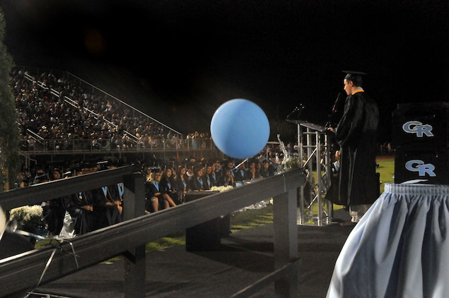 "Andrew Gough, son of Marine Attack Squadron 311 commanding officer Lt. Col. Michael Gough and Yuma, Ariz., Gila Ridge High School co-valedictorian, delivers a speech to his class during its graduation at Gila Ridge High School on April 28, 2010. The graduation, along with the graduations of Kofa High School and Yuma Catholic High School, was broadcast via the Web to VMA-311 Marines deployed with the 31st and 15th Marine Expeditionary Units. The broadcast was a combined effort between station personnel and local communications groups. ""We're treading new water,"" said Elena McShane, station school liaison. ""We know there are other schools in the country that are doing this, so why can't Yuma?"""