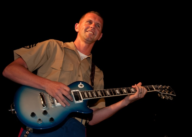 "WAIKIKI, Hawaii - Staff Sgt. Oscar L. Olive, guitarist with the U.S. Marine Corps Forces, Pacific Rock Band, plays Lady Gaga's ""Poker Face"" during the Military Band Mele, May 29, at the Fort DeRussy Parade Grounds, Waikiki, Hawaii. The Mele consisted of pop/ rock performances by Hawaii's Marine, Navy, Air Force and Army bands."