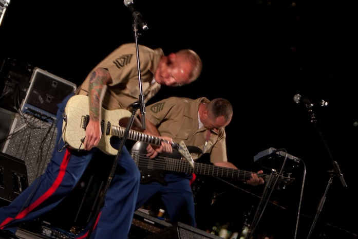 """WAIKIKI, Hawaii - Gunnery Sgt. Clint Walker, supply chief for Headquarters and Service Battalion, U.S. Marine Corps Forces, Pacific, and part time guitarist/ singer for the MarForPac Rock Band, and Staff Sgt. Chazz Harbison, bass guitarist, """"rock out"""" while performing Ozzy Osbourne's """"Crazy Train"""" during the Military Band Mele, May 29, at the Fort DeRussy Parade Grounds, Waikiki, Hawaii. The Mele consisted of pop/ rock performances by Hawaii's Marine, Navy, Air Force and Army bands."""