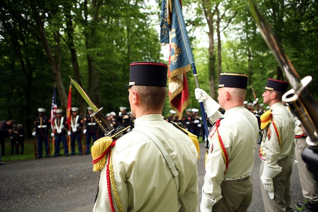 French honor guard soldiers stand in formation across from Marines with Fleet Anti-Terrorism Security Team Rota, Spain at the Iron Mike memorial area in the heart of Belleau Wood during a wreath laying ceremony in honor of the more than 1,800 Marines who died in the World War I Battle for Belleau Wood.