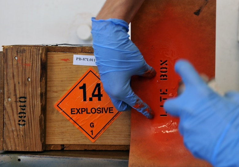 MOODY AIR FORCE BASE, Ga. -- A sticker is labeled with the weight of the explosive on the package while a specific color of paint is applied to the box during munitions inspector training course here Nov 1. The size and color of the explosive gives specific meaning to how the package should be transported and handled. (U.S. Air Force photo/Airman 1st Class Joshua Green)(RELEASED)