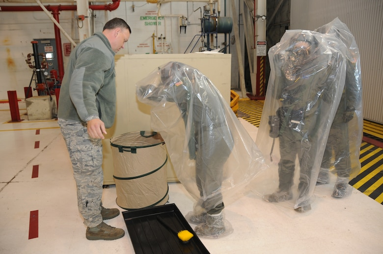 Tech. Sgt. John Wendelin from the 107th/914thAircrew Flight Equipment Squadron instructs flight crew from the 136th Airlift Squadron the proper technique in removal of their protective chemical bag. The Airmen were part of an operational readiness exercise recently conducted in preparation for the upcoming operational readiness inspection. (U.S. Air Force photo/Staff Sgt. Peter Dean)