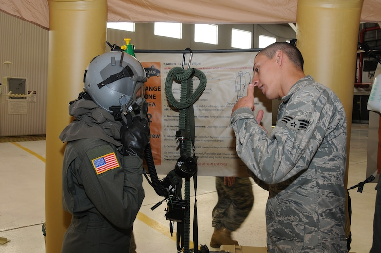 Senior Airman Shawn Niemira from the 107th Aircrew Flight Equipment Squadron instructs loadmaster Tech. Sgt. Katie Swanick from the 136th Airlift Squadron the proper technique in removal of flight helmet/mask. The two were part of an operational readiness exercise recently conducted in preparation for the upcoming operational readiness inspection. (U.S. Air Force photo/Staff Sgt. Peter Dean)