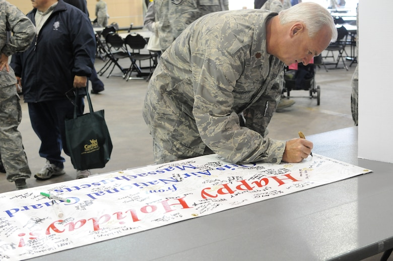 Major Michael McGourty, 102nd Medical Group, takes a moment during the 102nd Intelligence Wing Family Day, Oct. 3, 2010, to sign a 'Happy Holidays' banner that will be sent to the 102nd Security Forces Squadron Airmen who are serving in the Middle East.  The Airmen will be deployed through the Holiday Season.  (U.S. Air Force photo by Staff Sgt. Kerri Cole)
