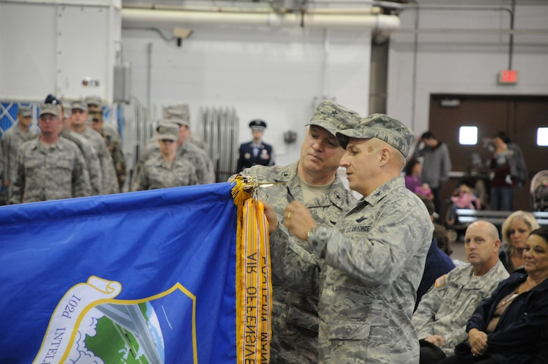 Brigadier General L. Scott Rice (left), Massachusetts Air National Guard commander, and Col. Anthony Schiavi (right), 102nd Intelligence Wing commander, add the 102nd Intelligence Wing's most recent Outstanding Unit Award banner to the 102nd Intelligence Wing flag, at the Wing's annual Family Day celebration, Oct. 3, 2010.  (U.S. Air Force photo by Master Sgt. Aaron Smith)