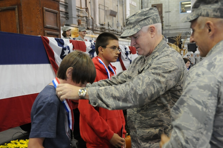 Brigadier General L. Scott Rice, Massachusetts Air National Guard commander, awards a medal to a child, Oct. 3, 2010, whose parent spent time away from home while deployed with the Air National Guard during the past year.  The medal presentation took place during the 102nd Intelligence Wing's annual Family Day where Airmen have an opportunity to teach their family members about what they do in the military and thank them for their dedicated support.  (U.S. Air Force photo by Airman 1st Class Luiz Vicentini)
