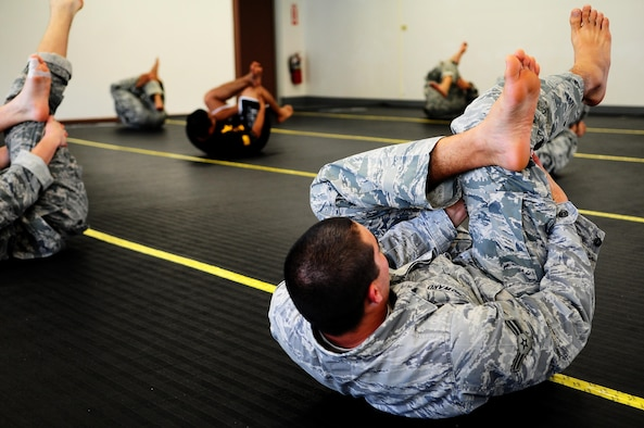 Airmen from the 736th Security Forces Squadron perform stretches during an Army Modern Combatives class hosted by the Guam Army National Guard at Fort Juan Muna, Oct. 20. The Airmen learned various styles of combative techniques including Jujitsu and grappling. (U.S. Air Force/Airman Jeffrey Schultze/Released)