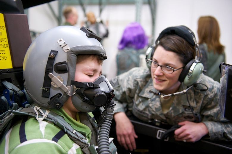 Keegan Hall, 12, breathes through an oxygen mask, Oct. 29, 2010, in the F-22 Raptor egress procedure trainer at Joint Base Elmendorf-Richardson with the help of Tech. Sgt. Chelsea De La Fuente. Sergeant DeLa Fuente is with the Aircrew Flight Equipment Flight, 3rd Operations Support Squadron. (U.S. Air Force photo/David Bedard)